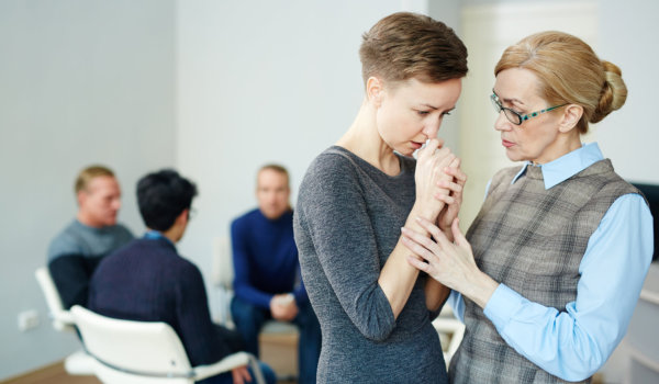 Female psychologist helping young women to stop crying